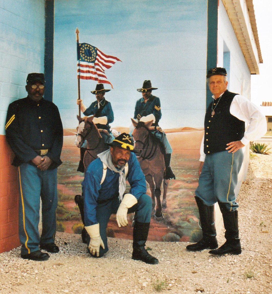 New Mexico Buffalo Soldiers pose in front of a Jal mural.